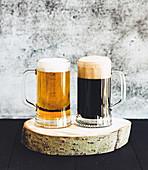 Dunkles und helles Bier in Krügen auf Birkenscheibe