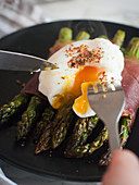 Grilled green asparagus wrapped in ham with a poached egg