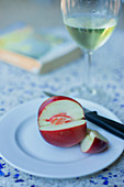 A white nectarine, sliced with a knife on a plate with a glass of white wine