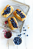 Puff pastry tartlets with jam and blueberries on a wire rack