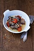 Kleine geschmorte Polpi mit Kirschtomaten, Knoblauch und getrockneten Peperoncini