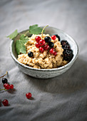 Warm, sweet quinoa risotto made with mango juice and decorated with fresh berries