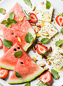 Summer watermelon, strawberry and feta cheese salad with wint leaves and pistachios