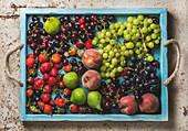Verschiedene Früchte auf blauem Holztablett