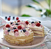 A crepe cake with two tone sour cream, berries and dried flowers (vegan)