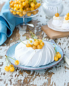 A pavlova with yellow cherries