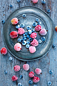 Frozen blueberries, gooseberries and raspberries on an old zinc plate
