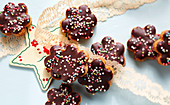 Jelly-filled almond flowers with chocolate glaze and sugar sprinkles
