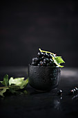 Blackcurrants in a black bowl