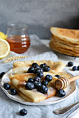 Classic French crepes topped with fresh blueberries and honey