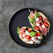 Piadina (Italian unleavened bread) with Parma ham, mozzarella and tomatoes