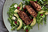 Crispy chicken on a mixed leaf salad with avocado