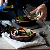 White wine being poured over a mussel dish