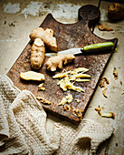 Ginger root and sliced ginger on rustic wooden board