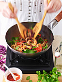 Woman Stir-Frying Chilli Prawns with Noodles
