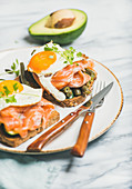 Healthy breakfast sandwich with salmon, avocado, fried egg, sauted green beans and fresh sprouts