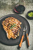 Grilled hot rib-eye beef steak on bone with chimichurri green sauce