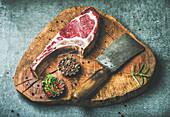 Rohes Dry Aged Ribeye Steak auf rustikalem Küchenbrett