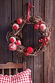 Weihnachtlicher Wandkranz aus Weidenzweigen und roten Kugeln