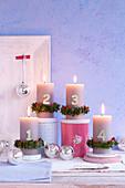 Adventskerzen dekoriert mit Zahlen und Buchskränzchen