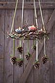 Hängender Adventskranz aus Ästen dekoriert mit Zapfen und Kerzen in Papierförmchen