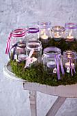 Mooskranz mit Teelichtern in Schraubgläsern als Adventskalender