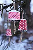 Selbstgemachte Vogelfutter-Station: Aufgehängte Pappbecher gefüllt mit Futter