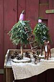Selbstgebastelte Bäumchen aus Nadelzweigen und Baumscheiben als winterliche Gartendekoration