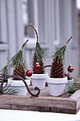Tannenzapfen weihnachtlich dekoriert mit Kieferhütchen und Mini-Baumkugeln