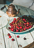 Plate of fresh ripe sweet cherries on rustic light blue wooden garden table
