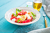 Simple summer caprese salad with mozzarella cheese, colouful tomatoes and fresh basil