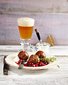 Meatballs with cranberry sauce and parsley sour cream