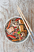 Yaki soba with tofu, bell pepper and mushrooms, sprinkled with green onion, sesame and fresh chili (glutenfree)