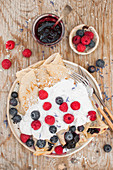 Vegan crepes with blueberry jam, whipped coconut cream and fresh berries
