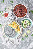 Vegan blue corn tacos, roasted pineapple, avocado with salad, black beans with tomato sauce