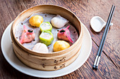 Assorted and colourful dim sum dumplings in a bamboo steamer on a wooden table with chopsticks