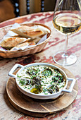 Plate of french escargot snails in a butter sauce with herbs with bread and wine in the background