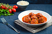 Plate of meatballs in tomato sauce with black pepper on a blue tablecloth with fork and ingredients in the background