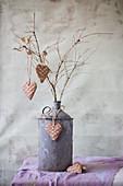 Dekoherzen mit Waffelmuster an einer alten Metallkanne mit Zweigen