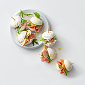 Bocconcini al prosciutto (small mozzarella sandwiches with ham, melon and mushrooms, Italy)