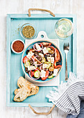 Greek salad with bread slices, oregano, pepper and glass of white wine