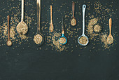Flat-lay of various old vintage kitchen spoons full of green uncooked buckwheat grains