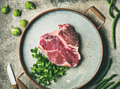 Uncooked dry-aged t-bone prime beef meat steak with fresh green parsley and smoked salt