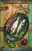 Raw sea bass with herbs and vegetables over rustic wooden background