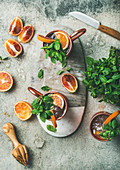 Blood orange Moscow mule alcohol cocktails with fresh mint leaves and ice in copper mugs