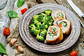Turkey rolls filled with ricotta, spinach and tomato served with blanched broccoli florets