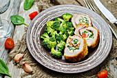 Putenröllchen mit Ricotta-Spinat-Tomaten-Füllung, dazu blanchierte Broccoliröschen