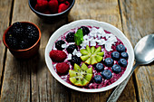 A breakfast bowl with blueberry smoothies, blueberries, kiwi, raspberries, blackberries and coconut flakes
