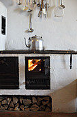 Kettle on wood-fired cooker in kitchen of mountain cabin