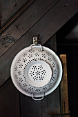 Vintage enamel colander hung from wooden wall